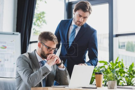 Photo for Young concentrated businessmen using laptop and working together - Royalty Free Image