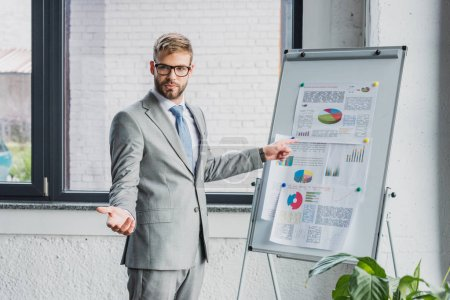 handsome young businessman in suit and eyeglasses pointing at whiteboard with charts and looking at camera