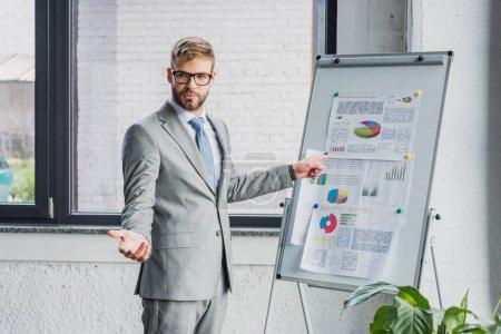 Photo pour Beau jeune homme d'affaires en costume et lunettes pointant sur tableau blanc avec des graphiques et en regardant la caméra - image libre de droit
