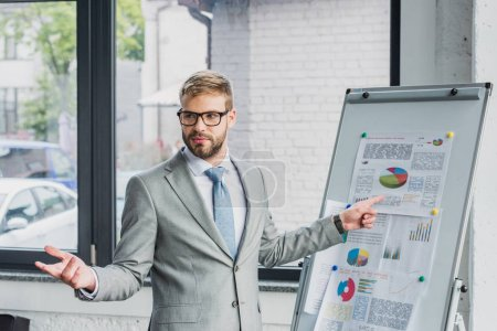 handsome young businessman in suit and eyeglasses pointing at whiteboard with charts and looking away