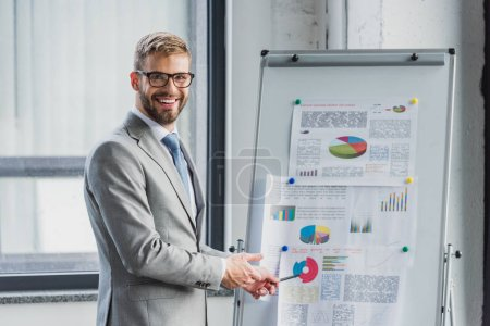 handsome young businessman in suit and eyeglasses pointing at whiteboard with charts and smiling at camera