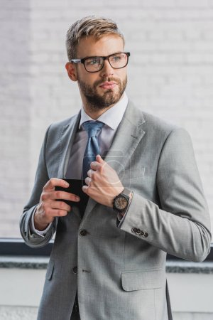 handsome young businessman in suit and eyeglasses holding smartphone and looking away