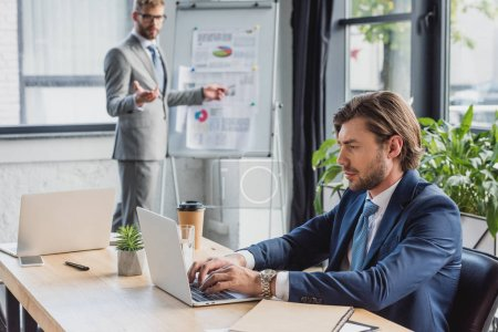 young businessman using laptop while colleague standing near whiteboard behind