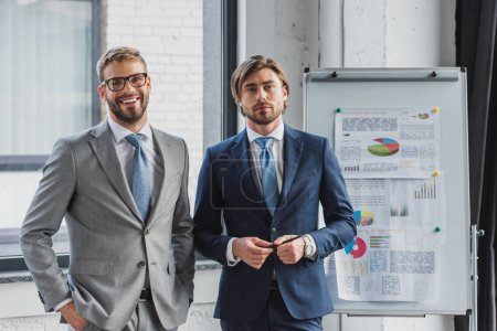 Photo for Three handsome young businessmen in suits standing together and looking at camera in office - Royalty Free Image
