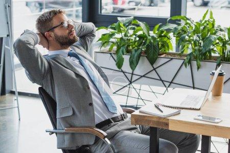 Photo pour Jeune homme d'affaires en costume et lunettes assis avec les mains derrière la tête dans le Bureau - image libre de droit
