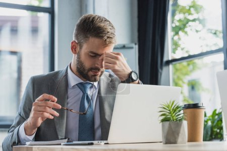 tired young businessman holding eyeglasses and rubbing nose bridge while using laptop in office