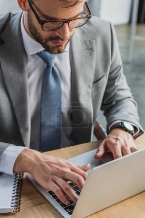 Photo for High angle view of businessman in eyeglasses using laptop in office - Royalty Free Image