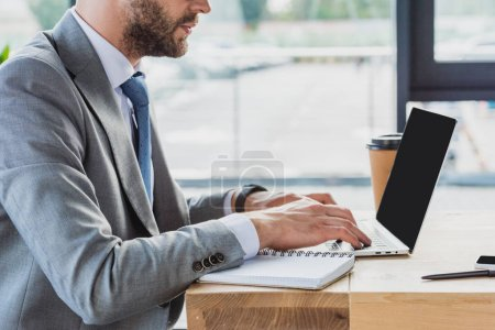 Photo for Cropped shot of businessman in suit using laptop with blank screen in office - Royalty Free Image