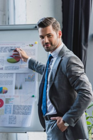 confident young businessman pointing at whiteboard with business charts and smiling at camera