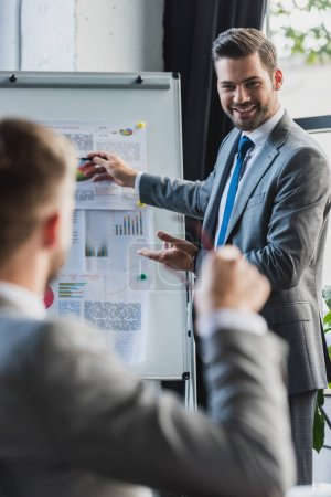 Photo for Selective focus of smiling young businessman pointing at whiteboard with business charts and looking at colleague sitting on foreground - Royalty Free Image