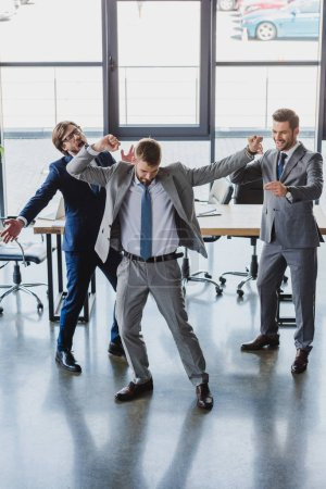Photo for Excited young businessmen dancing and celebrating in office - Royalty Free Image