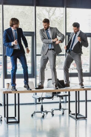 three smiling young businessmen dancing on table in office