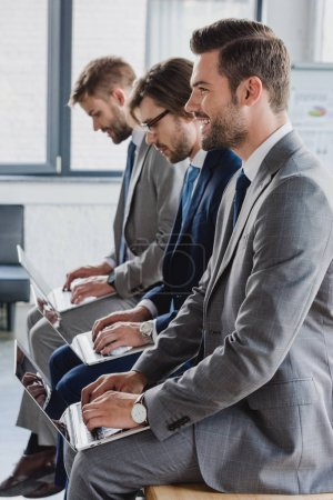 side view of handsome young businessmen in suits sitting and using laptops in office