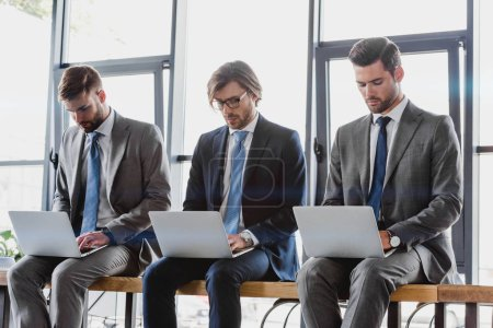 Photo for Three young businessmen in suits sitting and using laptops - Royalty Free Image