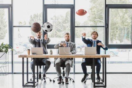 Photo pour Employés de bureau jeunes jetant des boules tout en travaillant avec des ordinateurs portables au bureau - image libre de droit