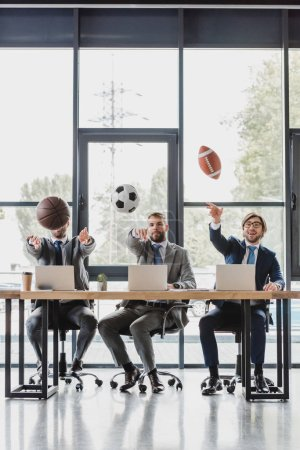 Photo for Young businessmen throwing balls while working with laptops in office - Royalty Free Image