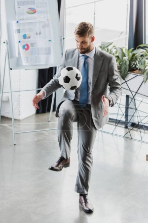 full length view of young businessman in formal wear playing with soccer ball in office