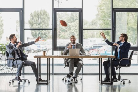 smiling young businessmen using laptops and playing with soccer and rugby balls in office