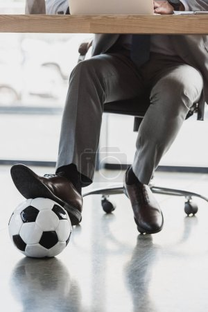 cropped shot of young businessman with soccer ball using laptop in office