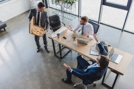 high angle view of young businessman holding pizza in box and looking at coworkers in office