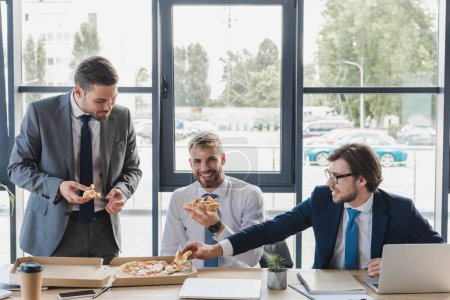 happy young office workers eating pizza at workplace