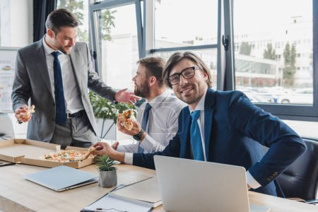 smiling young businessmen eating pizza at workplace