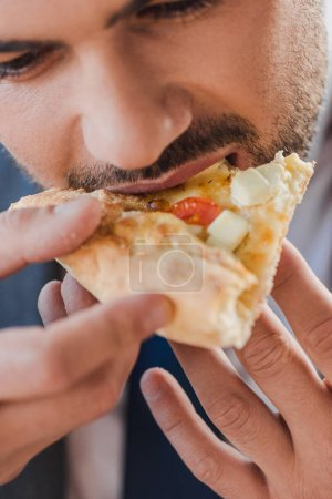 cropped shot of young businessman eating pizza