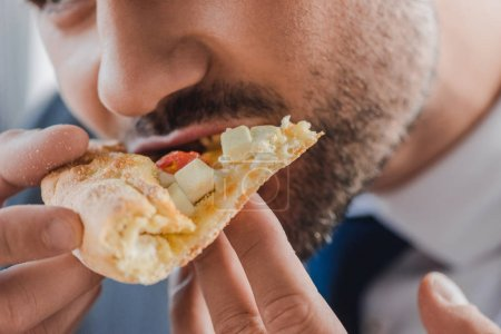 close-up view of young businessman eating pizza