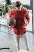 high angle view of businessman holding basketball ball and using smartphone in office