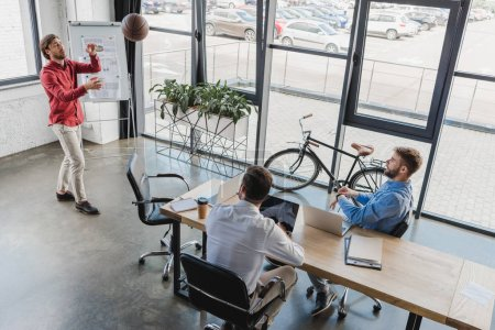 high angle view of young businessmen playing with basketball ball and using laptops in office
