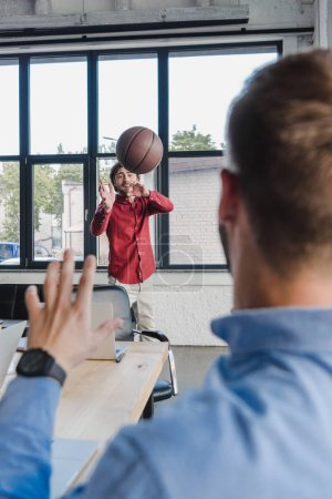 Photo for Selective focus of young businessmen playing with basketball ball in office - Royalty Free Image