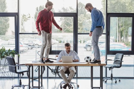 young businessman using laptop while colleagues playing with soccer ball on table