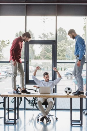 triumphing businessman using laptop while colleagues playing with soccer ball on table