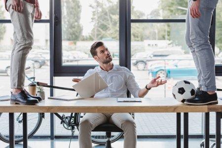 Photo pour Vue partielle des hommes botter le ballon de soccer sur table et collègue irrité à l'aide d'ordinateur portable au bureau - image libre de droit
