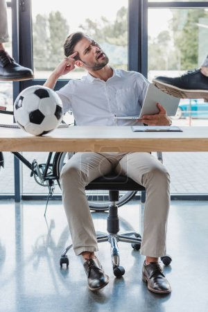 Photo for Cropped shot of men kicking soccer ball on table while angry colleague using laptop in office - Royalty Free Image