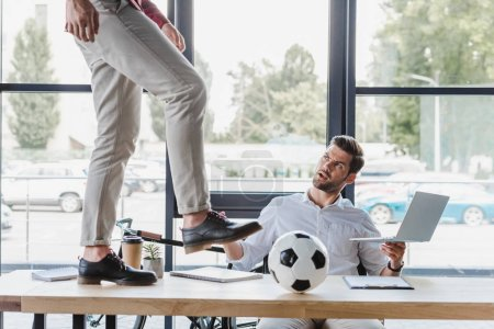 cropped shot of man kicking soccer ball on table while colleague using laptop in office