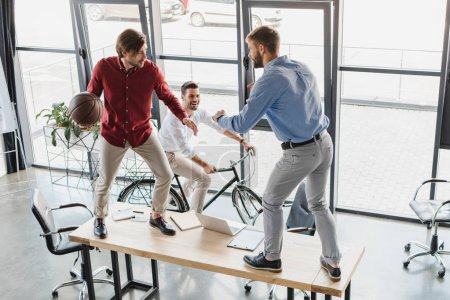 high angle view of young businessmen having fun with basketball ball in office