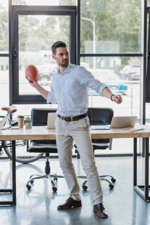 Photo pour Beau jeune homme d'affaires jouant avec ballon de rugby au bureau - image libre de droit