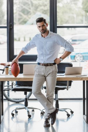 handsome young businessman holding rugby ball in office