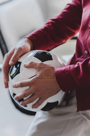 Photo pour Recadrée tir d'homme d'affaires en tenant le ballon de foot au bureau - image libre de droit