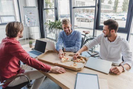 happy young businessmen eating pizza at workplace