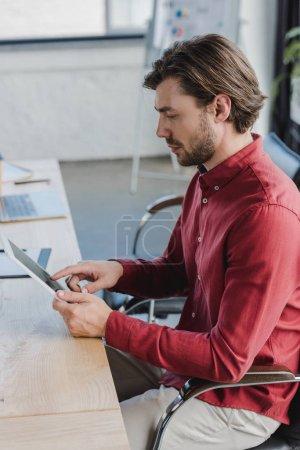 Photo pour Vue de côté du jeune homme d'affaires assis et à l'aide de tablette numérique au bureau - image libre de droit