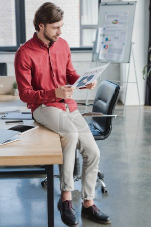 handsome young businessman sitting on table and reading business newspaper in office
