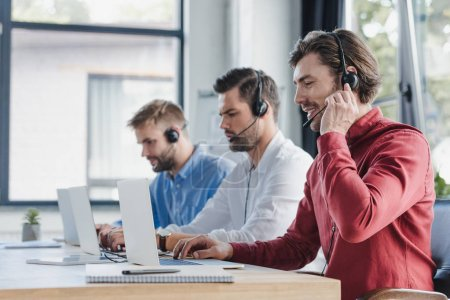 three young call center operators in headsets using laptops in office