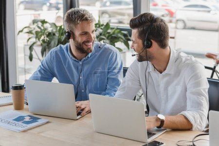 handsome young call center operators in headsets smiling each other while using laptops in office