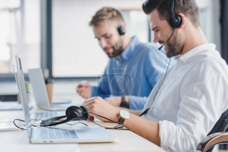 Photo for Smiling young call center operators in headsets using laptops in office - Royalty Free Image