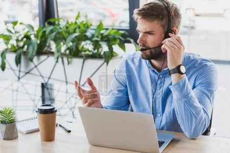 handsome young call center operator in headset working with laptop in office