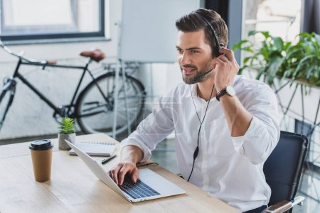 handsome smiling young call center operator in headset using laptop and looking away in office