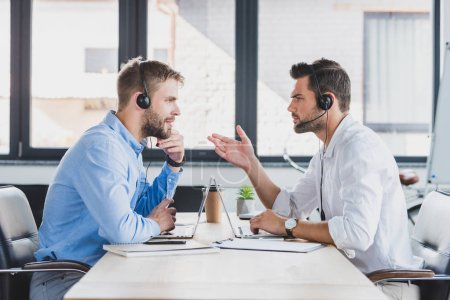 Photo for Side view of young call center operators in headsets discussing and looking at each other while using laptops in office - Royalty Free Image