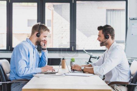 vue latérale du sourire des opérateurs de centres d'appel jeunes de casques d'écoute à l'aide d'ordinateurs portables au bureau